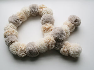 A gorgeous pompom scarf. Making 4 pompoms at a time, thread them densly onto a cord to make this snuggly fluffy scarf.
