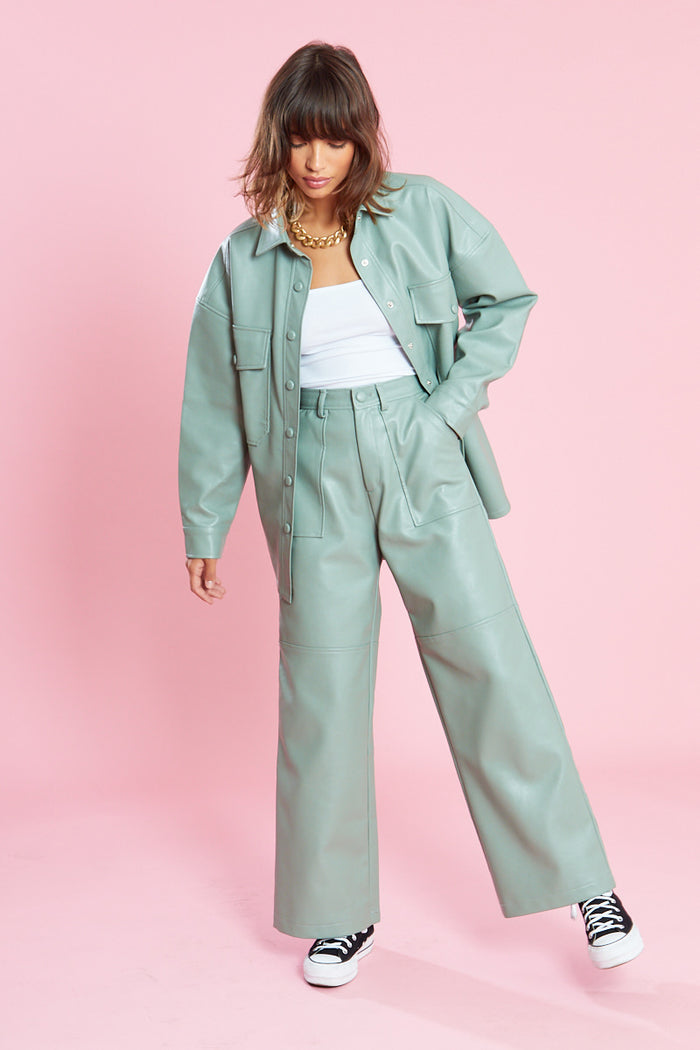Woman wearing mint green leather jacket and trousers co-ord set