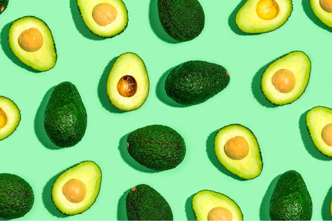 Half avocados on a bright green background.