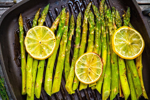 Grilled asparagus on a skillet pan with lemon slices