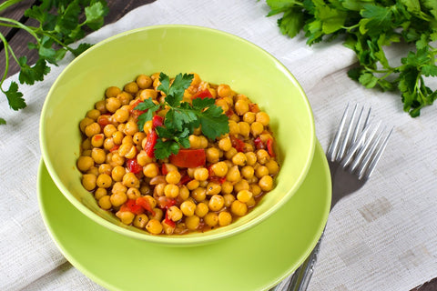Cooked chickpeas in bright green bowl.