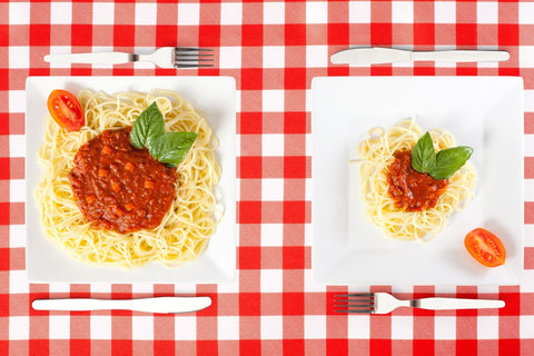 Two different portion sizes of spaghetti on white plates against a red and white checkered table cloth.