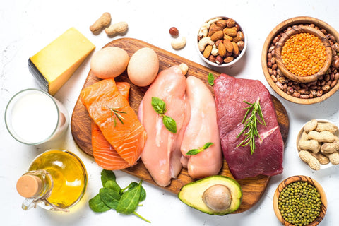 Cutting board with different types of protein like meat, fish, eggs, avocados.