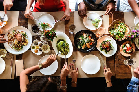Group of friends out to dinner together beginning to fill up their plates with food.