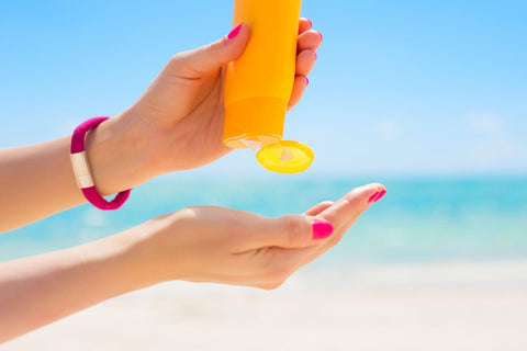 Young woman applying sunscreen at the beach on a sunny day.