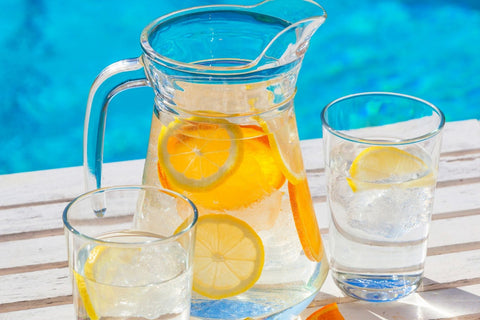 Pitcher of water with oranges and lemons inside with two glasses.