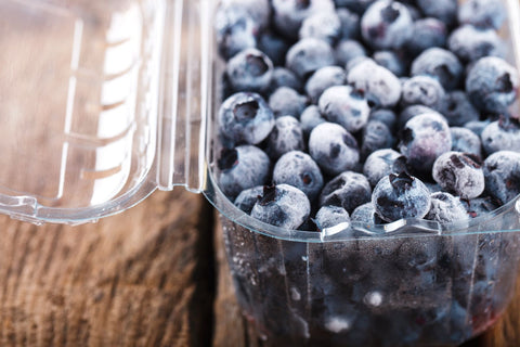 Carton of blueberries against a dark wood background.