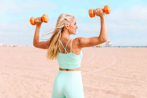 Rebecca dressed in a aqua matching workout set holding two orange weights in an overhead press position at the beach.