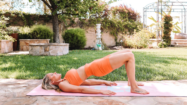Rebecca Louise laying down on her yoga matt on her in her back yard performing a glute bridge