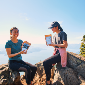 mikayla and friend hold backcountry meals and pose on top of a mountain with ocean in the background