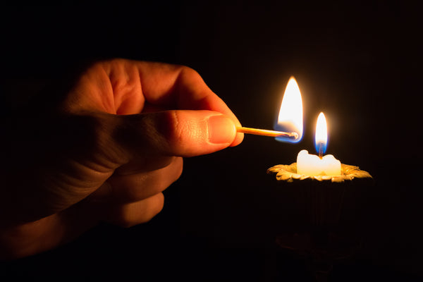 hand lighting a candle in the dark with match