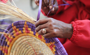 The basket weaving process. An artisan making a hand-woven basket.