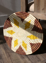 Buna Basket - a flat, hand-woven basket displayed on the floor