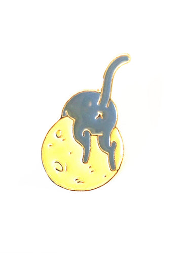 gray cat laying over a yellow moon enamel pin