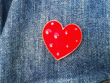 closeup view of heart pin on a jean jacket