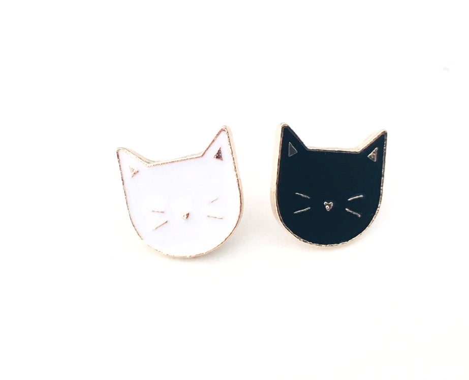 Close up front view of mini black & white enamel cat face pins