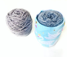 top down view of one ball of yarn neatly covered with skein coat and one ball of yarn without yarn bowl