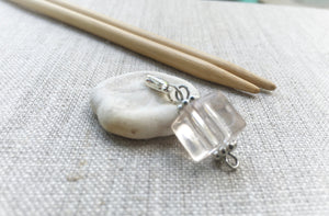 side view of clear acrylic cube stitch marker with silver lobster clasp
