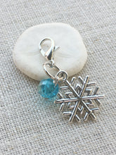 detailed closeup of silver toned stitch marker with aqua acrylic bead detail tool for knitting and crochet
