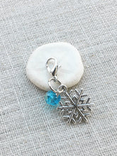sfront view of silver tone snowflake place holder with ice blue acrylic bead detail and lobster claw closure