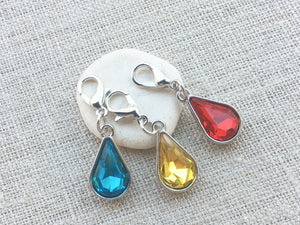 close up frontal view of jewel toned red, yellow and blue faux crystal teardrop markers