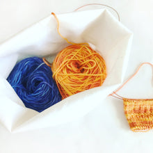 open bag with 2 full skeins of yarn to shown how much room each bag has