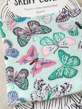 close up photo pink, green ball and blue butterflies printed on mint green cotton fabric