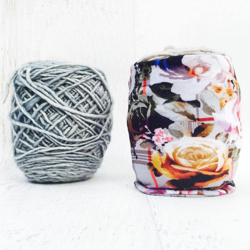 large romantic flowers on a bed of soft gray fabric covers a ball of yarn