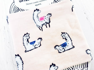 close up view of cotton pink fabric printed with alpacas