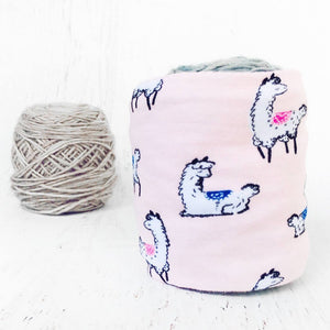 white alpacas on a light pink cotton fabric shown covering a ball of yarn