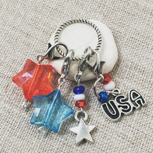 closeup frontal view of stitch markers charm set with patriotic red white and blue charms