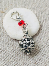 detailed back view of floral detail on silver toned ball stitch marker