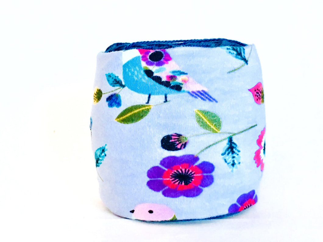 pink and purple flowers with colorful birds on cotton fabric cover this yarn organizer