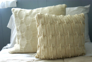 set of cable knit pillows shown sitting on a bed