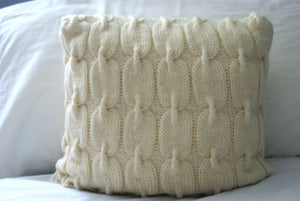 close up the cable knit pattern used to knit this pillow sham