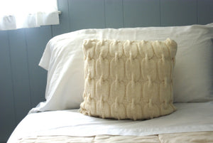 cable knit pillow shown displayed on a bed for decor