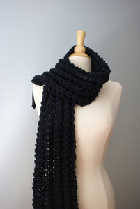 chunky scarf shown in black thrown over one shoulders