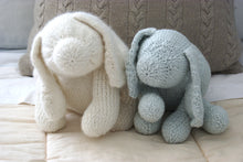 2 finished knitted dog toys sitting adorably side by side on a Childs bed
