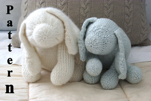close up pictures of 2 knit dogs sitting on a Childs bed one blue and one white dog