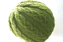 green cable knit hat pattern shown on the head of a mannequin
