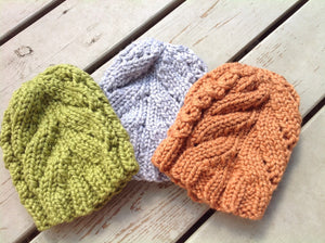 Chunky Surf City cable knit hat pattern shown in orange green and gray