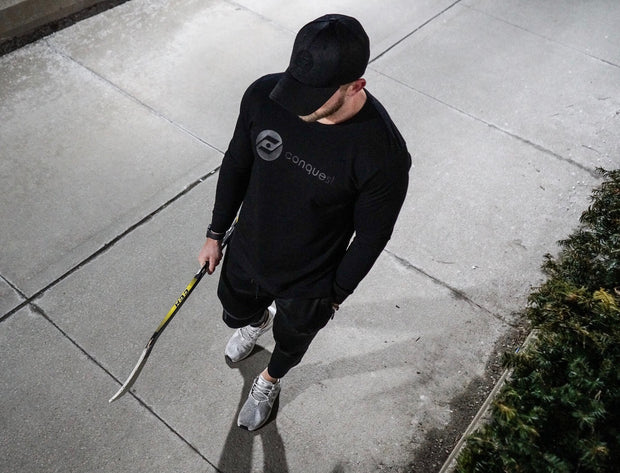 Challenger Sweater (black) holding stick