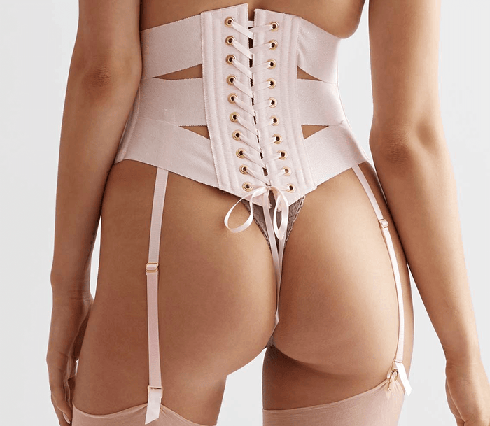 Corset lacing on pink underbust ribbon corset with garter straps and gold garter clips