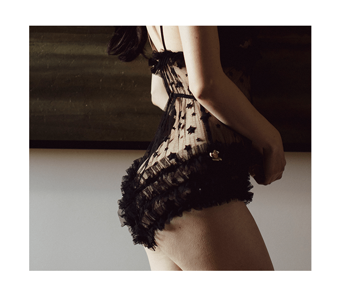 Fine vintage inspired lingerie teddy in sheer black star lace with ruffled back detail