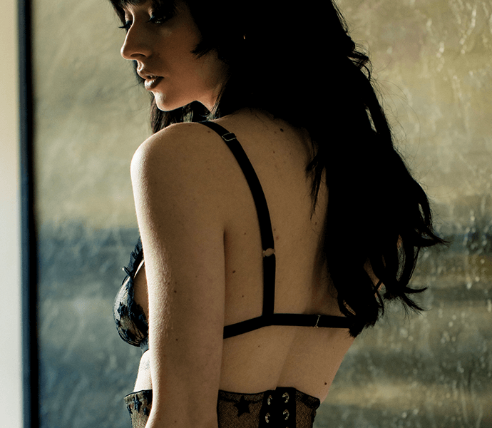 Back straps on sheer ruffled triangle bralette worn with vintage style garter belt