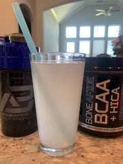 a glass of BCAA+HICA mixed with water stands on a counter in front of the product jar and a sports drink container