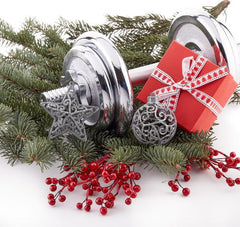 silver dumbbell, red package, holly berries and evergreens