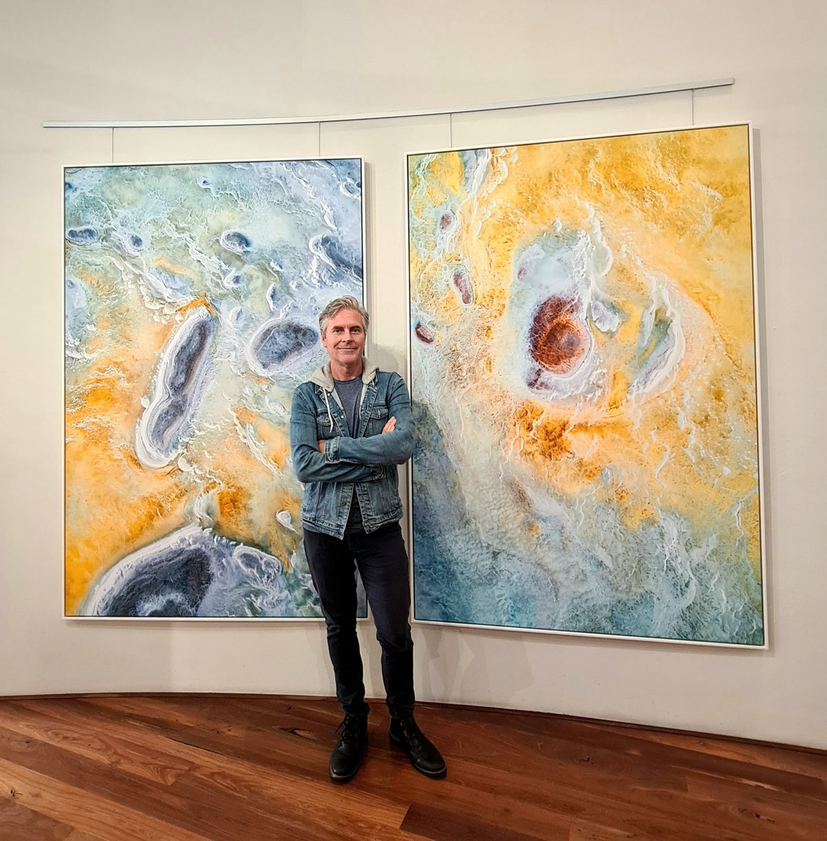 Christian Fletcher standing in front of two large 2m aerial photographs printed on canvas.