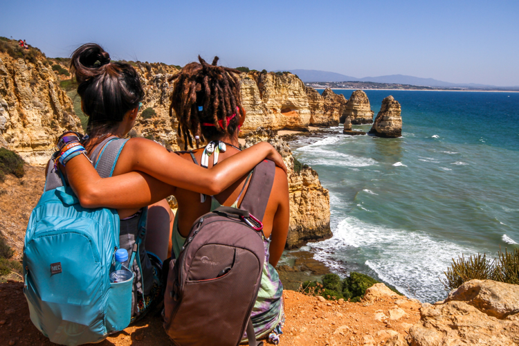 Two friends wearing backpacks with their arms around one another, looking out at the ocean