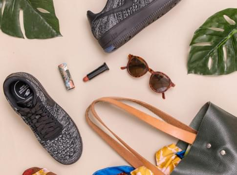 Shoes, lipstick, sunglasses and a purse creating a floor spread